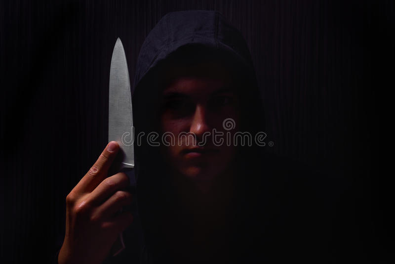 Retrato del primer de un hombre joven en una sudadera con capucha, sosteniendo un cuchillo adentro foto de archivo libre de regalías