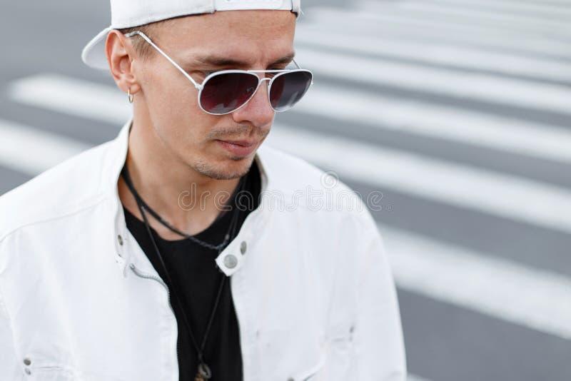 Retrato del primer de un hombre joven del inconformista en una chaqueta blanca de moda en una camiseta negra en una gorra de béis imagen de archivo libre de regalías