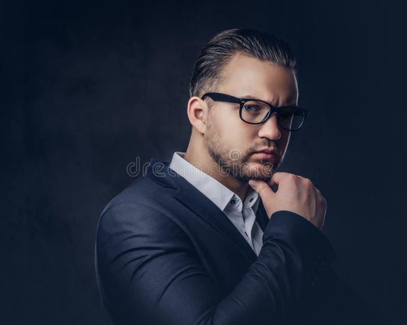 Retrato del primer de un hombre de negocios elegante pensativo con la cara seria en un traje formal elegante y vidrios en una osc foto de archivo
