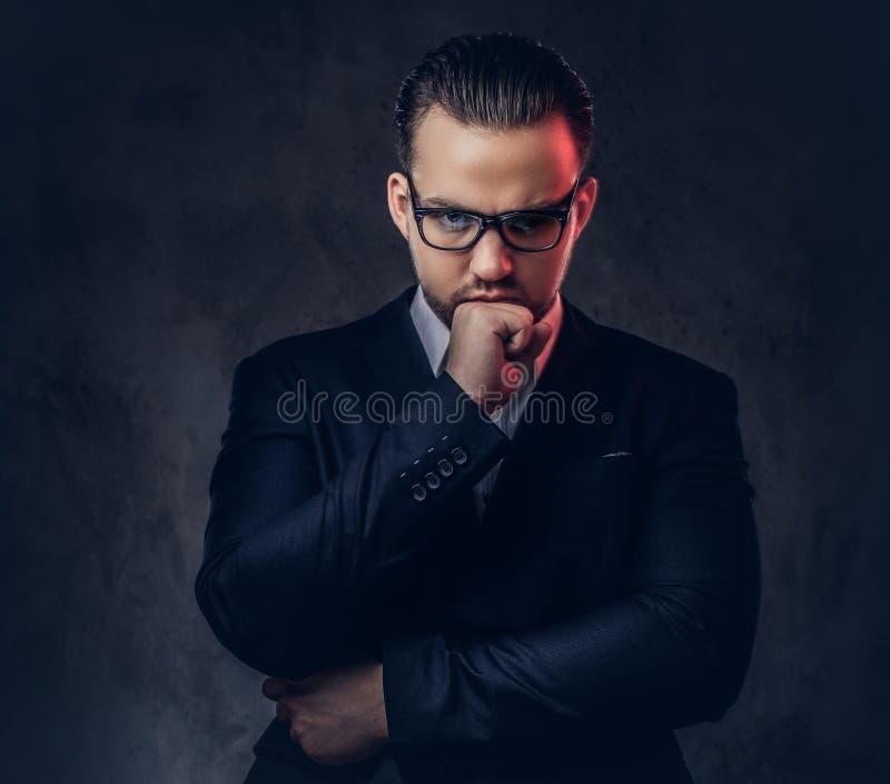 Retrato del primer de un hombre de negocios elegante pensativo con la cara seria en un traje formal elegante y vidrios en una osc imagen de archivo libre de regalías