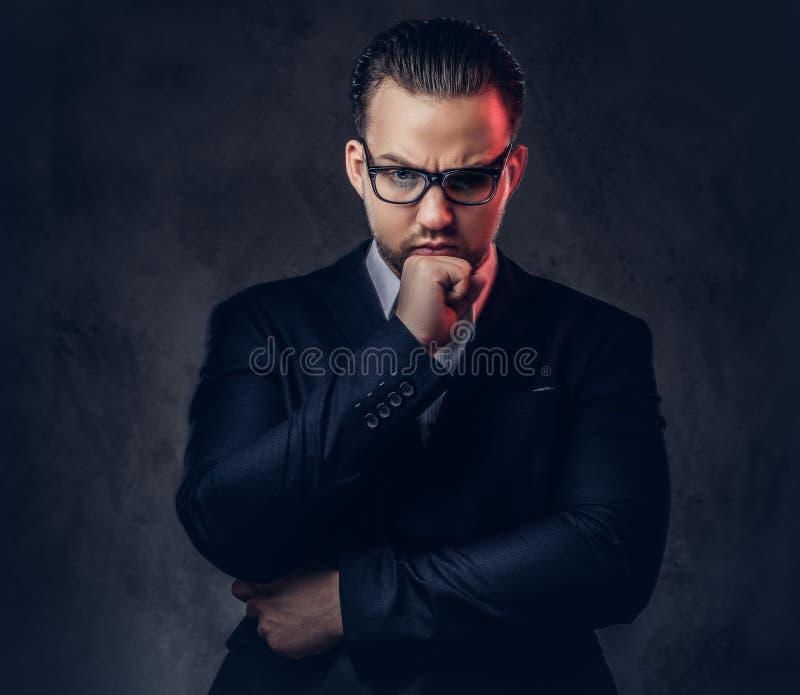 Retrato del primer de un hombre de negocios elegante pensativo con la cara seria en un traje formal elegante y vidrios en una osc imagenes de archivo