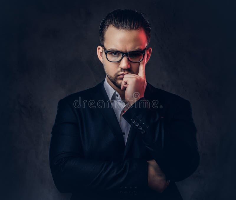 Retrato del primer de un hombre de negocios elegante pensativo con la cara seria en un traje formal elegante y vidrios en una osc fotos de archivo