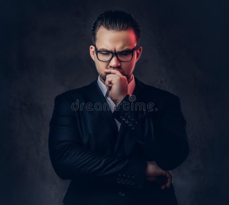 Retrato del primer de un hombre de negocios elegante pensativo con la cara seria en un traje formal elegante y vidrios en una osc foto de archivo libre de regalías