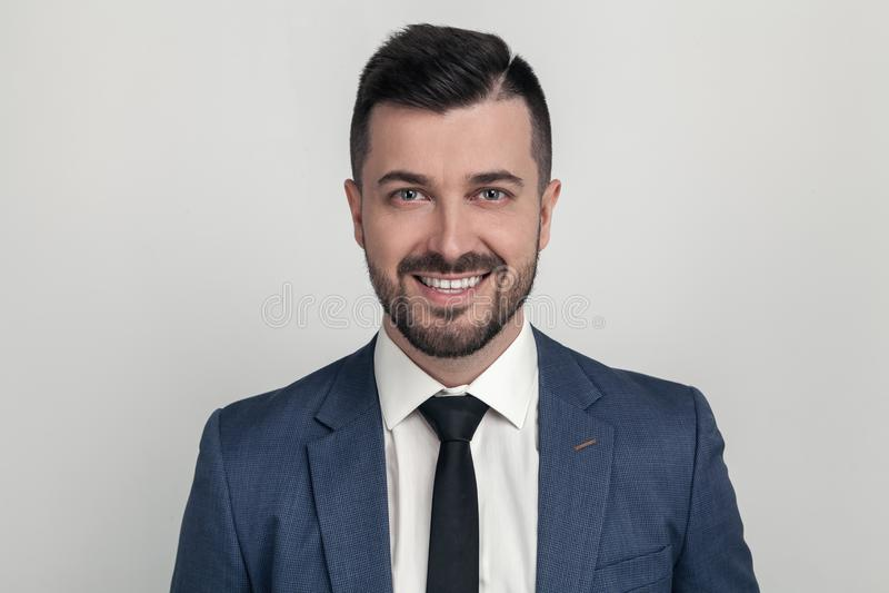 Retrato del primer de un hombre de negocios hermoso que sonríe en la cámara Vestido en un traje En un fondo blanco fotografía de archivo libre de regalías