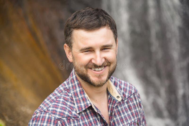 Retrato del primer de un inconformista sonriente barbudo contra un fondo de la cascada imagen de archivo
