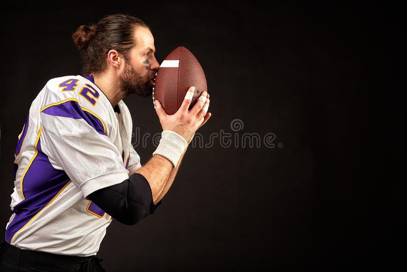 Retrato del primer de un jugador agresivo del jugador de fútbol americano que ruega en su bola Concentración antes del juego foto de archivo libre de regalías