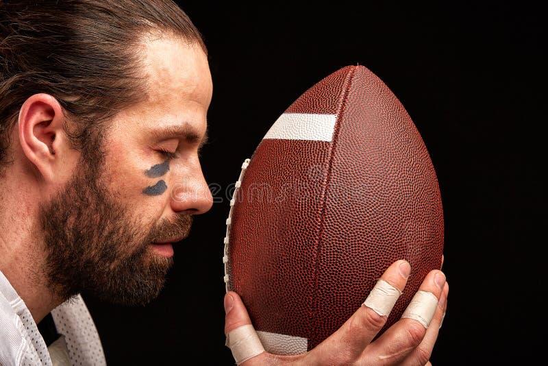 Retrato del primer de un jugador agresivo del jugador de fútbol americano que ruega en su bola Concentración antes del juego foto de archivo