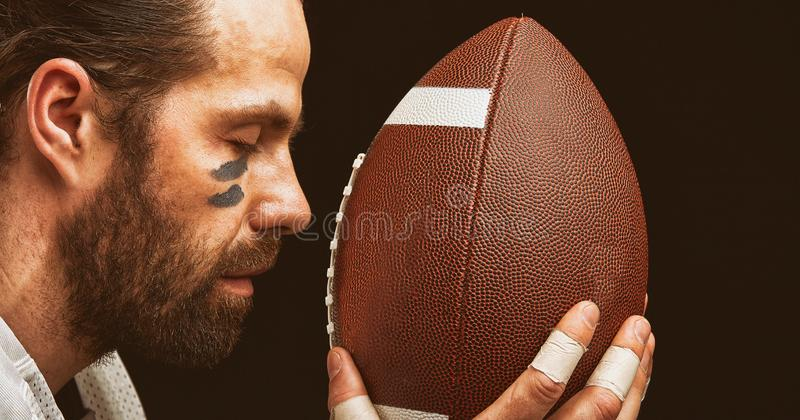 Retrato del primer de un jugador agresivo del jugador de fútbol americano que ruega en su bola Concentración antes del juego imagen de archivo
