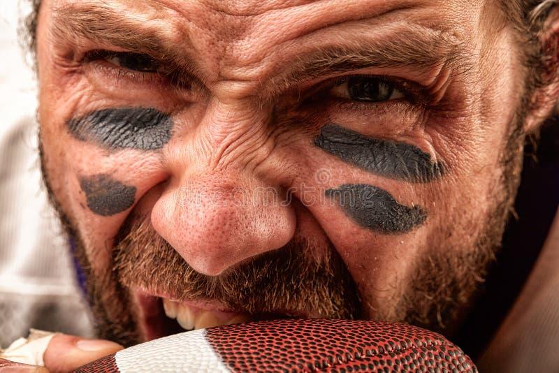 Retrato del primer de un jugador de fútbol americano agresivo El jugador agresivo muerde su bola r imágenes de archivo libres de regalías