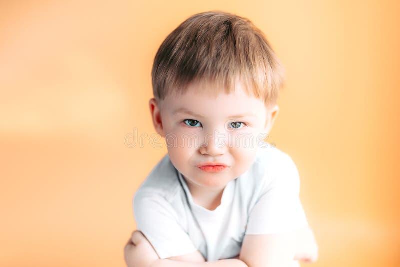 Retrato del primer de un muchacho enojado con sus brazos doblados en fondo anaranjado fotos de archivo libres de regalías