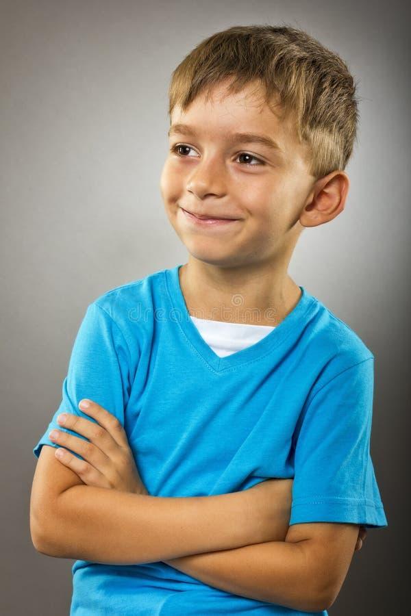 Retrato del primer de un niño pequeño lindo con los brazos doblados imagen de archivo libre de regalías