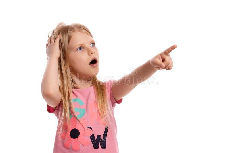 Retrato del primer de un niño rubio agradable en una presentación rosada de la camiseta aislado en el fondo blanco fotografía de archivo libre de regalías