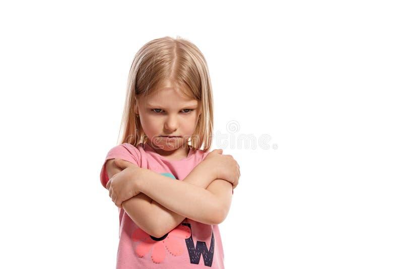 Retrato del primer de un niño rubio agradable en una presentación rosada de la camiseta aislado en el fondo blanco foto de archivo