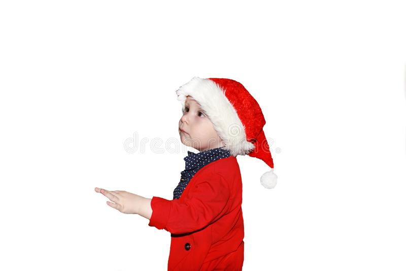 Retrato del primer de un pequeño bebé lindo que lleva el sombrero rojo de Santa Claus aislado en el fondo blanco, traje tradicion imagenes de archivo
