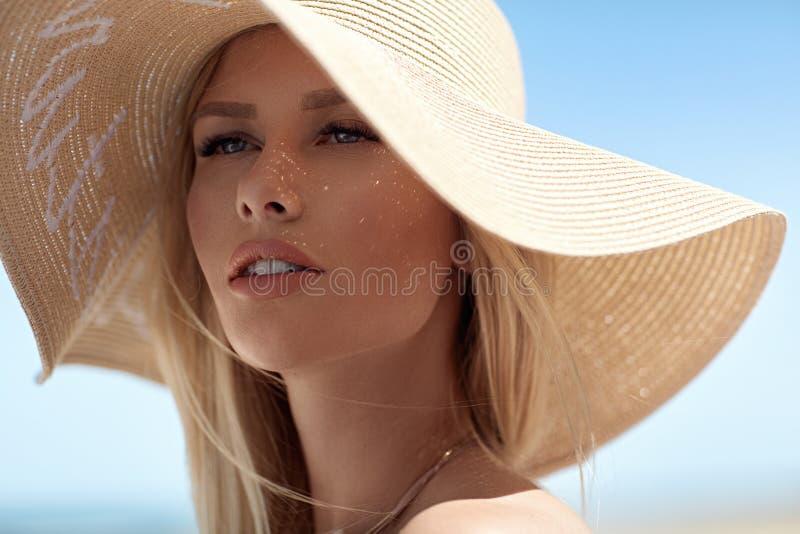 Retrato del primer de un rubio sensual llevando un sombrero de paja fotografía de archivo libre de regalías