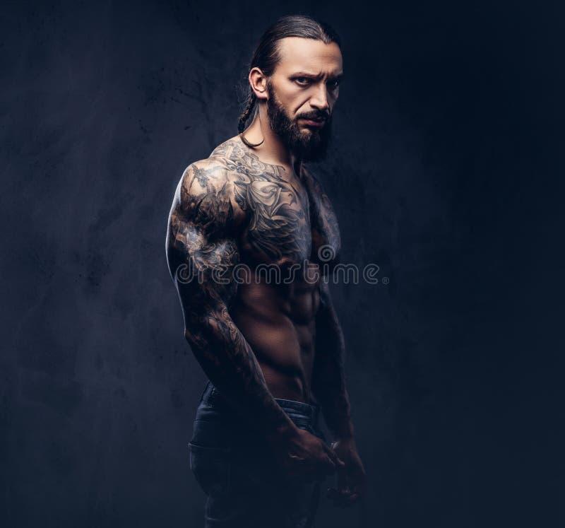Retrato del primer de un varón tattoed barbudo desnudo muscular con un corte de pelo elegante, aislado en un fondo oscuro imagenes de archivo