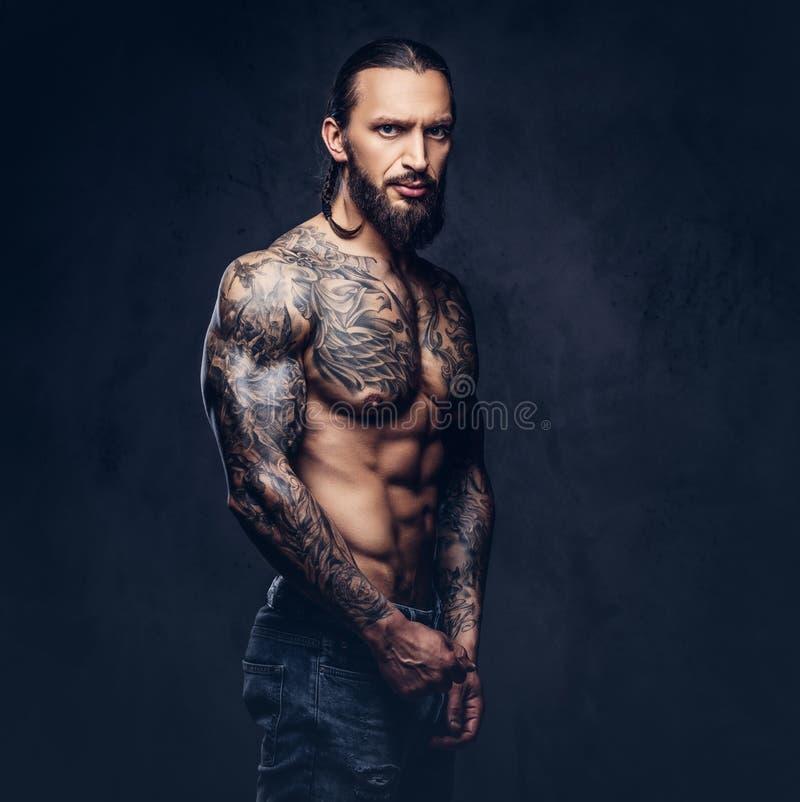 Retrato del primer de un varón tattoed barbudo desnudo muscular con un corte de pelo elegante, aislado en un fondo oscuro imagen de archivo