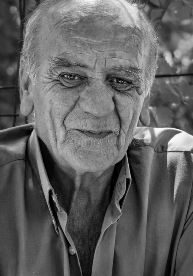 Retrato del primer de un viejo varón jubilado griego serio que fuma un cigarrillo con una sonrisa, en blanco y negro imagen de archivo