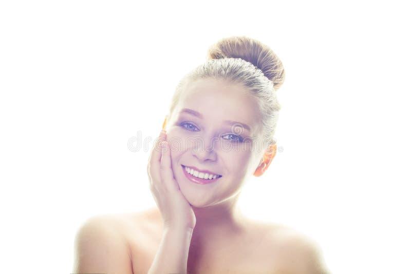 Retrato del primer de una cara hermosa de la mujer con su mano en su mejilla aislada en el fondo blanco Cosméticos, maquillaje y  imágenes de archivo libres de regalías