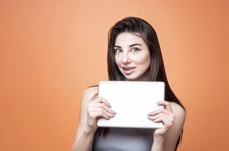 Retrato del primer de una muchacha morena emocionada joven con la tableta en sus manos que miran la cámara con la boca abierta imágenes de archivo libres de regalías