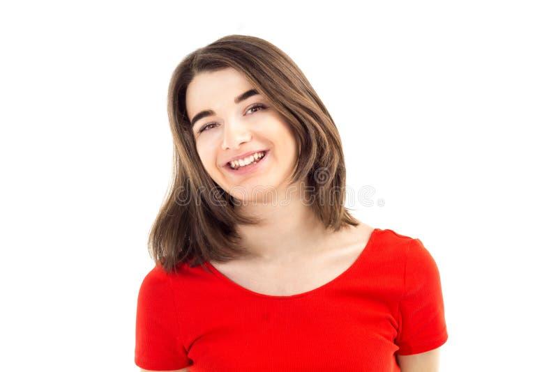 Retrato del primer de una muchacha sonriente feliz joven en camiseta roja contra el fondo, la forma de vida y el concepto blancos foto de archivo libre de regalías