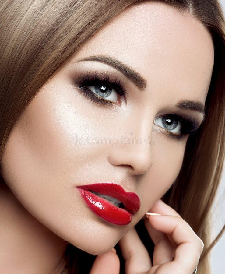 Retrato del primer de una mujer elegante con maquillaje brillante, labios rojos, latigazos largos, pelo largo recto, cejas perfec imagenes de archivo