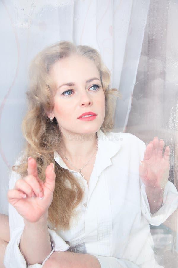 Retrato del primer de una mujer hermosa triste cerca de la ventana imagenes de archivo