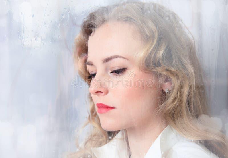 Retrato del primer de una mujer hermosa triste cerca de la ventana fotografía de archivo
