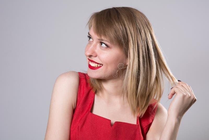 Retrato del primer de una mujer joven sonriente que mira lejos imagen de archivo