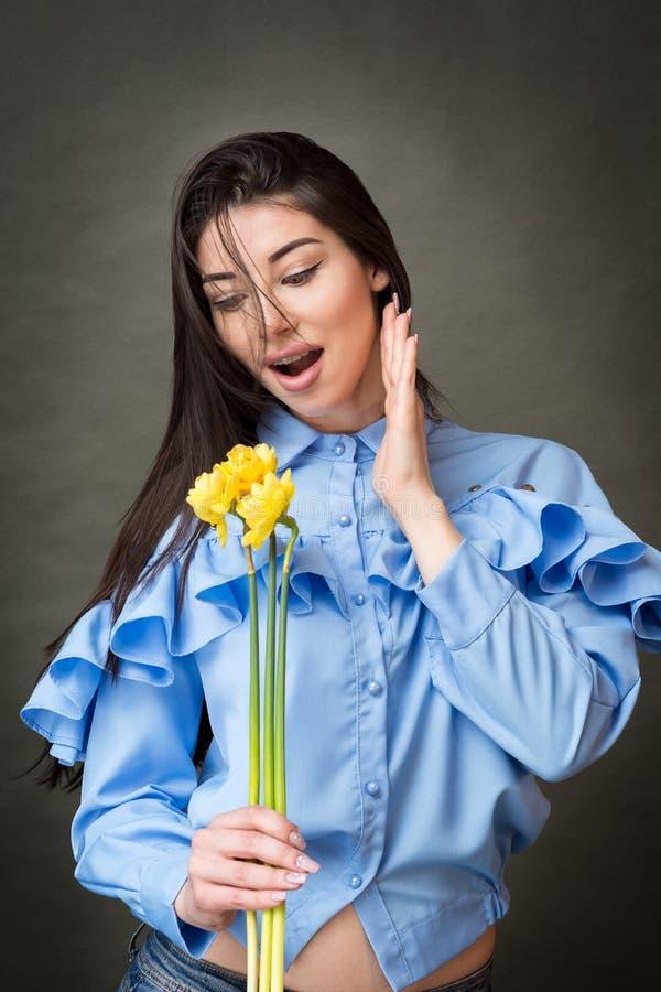 Retrato del primer de una mujer morena feliz hermosa en la camisa azul que sostiene junquillos amarillos en sus manos y que sonrí imágenes de archivo libres de regalías