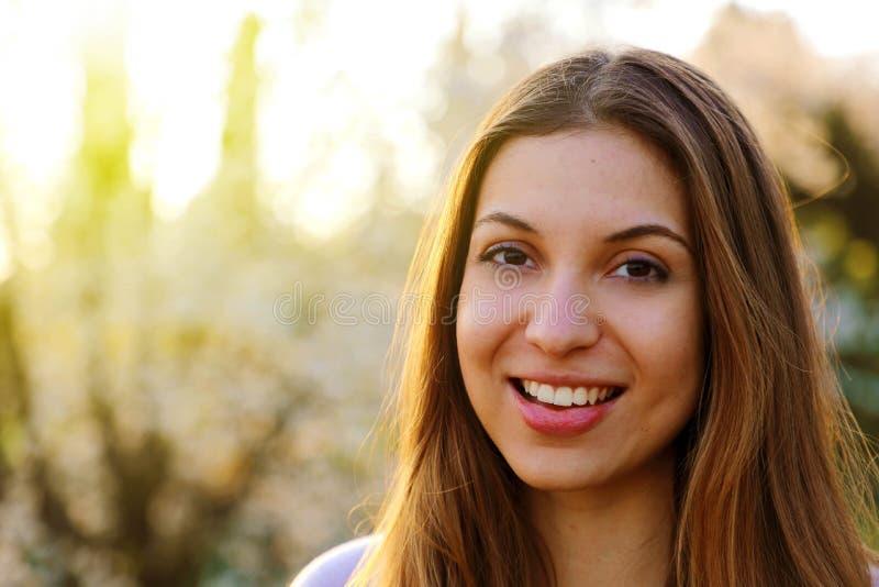 Retrato del primer de una mujer morena joven amistosa hermosa al aire libre en tiempo de primavera fotos de archivo libres de regalías