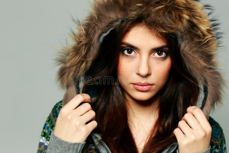 Retrato del primer de una mujer pensativa joven en equipo caliente del invierno imagenes de archivo
