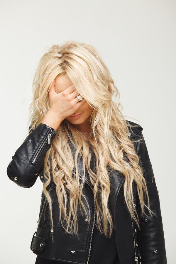 Retrato del primer de una mujer rubia con el pelo largo que cubre su cara con una mano en vergüenza culpabilidad, decepción foto de archivo libre de regalías