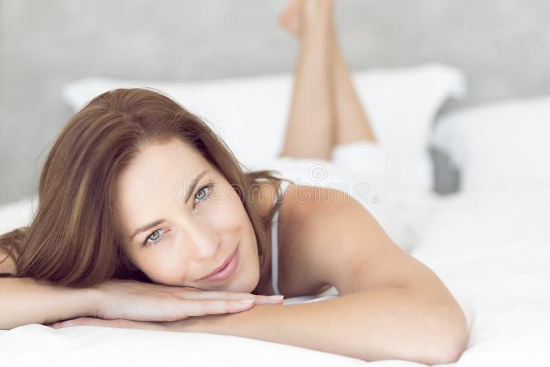 Retrato del primer de una mujer sonriente bonita que miente en cama fotos de archivo