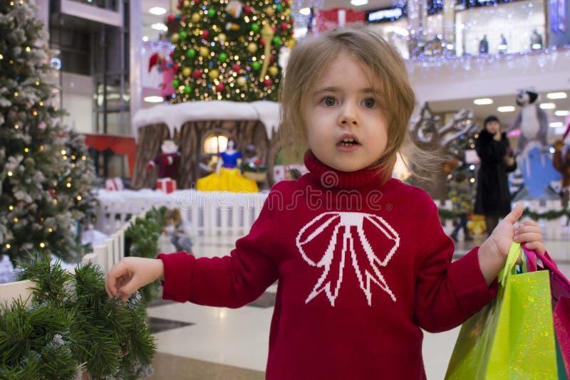 Retrato del primer de una niña bonita en un suéter rojo con los regalos en un fondo de la Navidad alameda de compras encendido foto de archivo libre de regalías