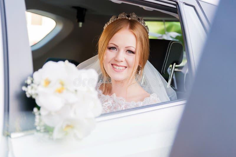 Retrato del primer de una novia hermosa en una ventanilla del coche de la boda El concepto de felicidad de la boda foto de archivo