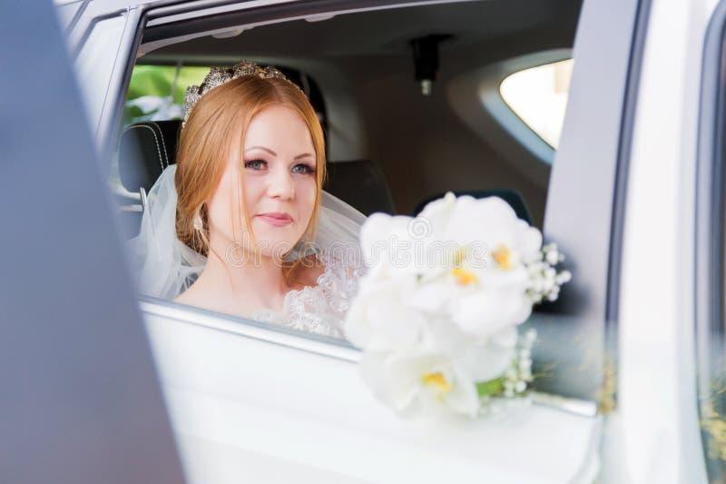 Retrato del primer de una novia hermosa en una ventanilla del coche de la boda El concepto de felicidad de la boda imagen de archivo