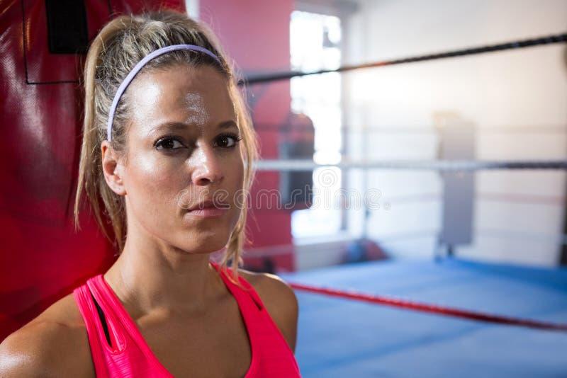 Retrato del primer del atleta de sexo femenino joven contra el ring de boxeo imagenes de archivo