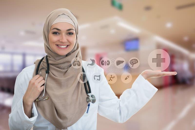 Retrato del primer del doctor de sexo femenino musulmán confiado amistoso, sonriente que lleva a cabo símbolos médicos imagen de archivo libre de regalías