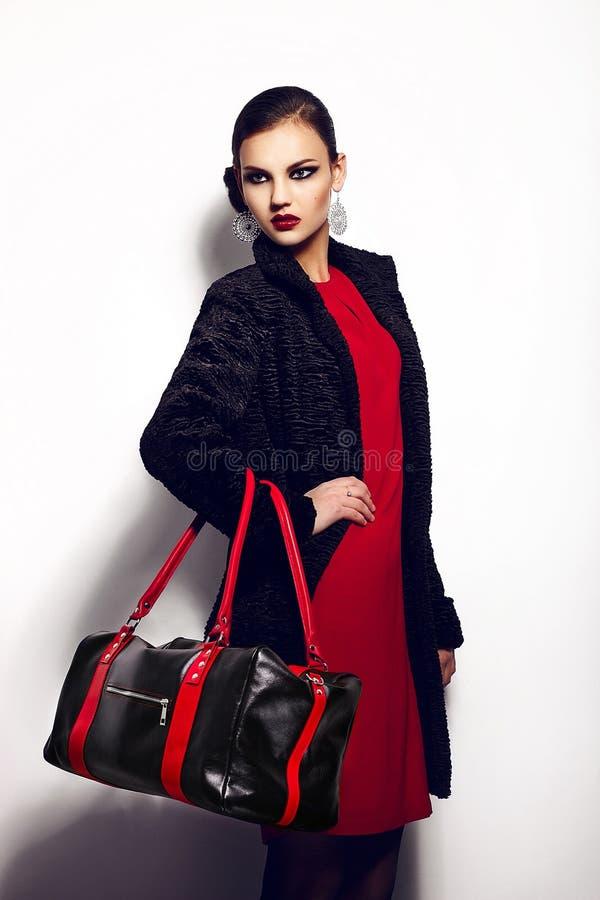 Retrato del primer del encanto del modelo caucásico moreno elegante atractivo hermoso de la mujer joven en vestido rojo con b negr fotografía de archivo
