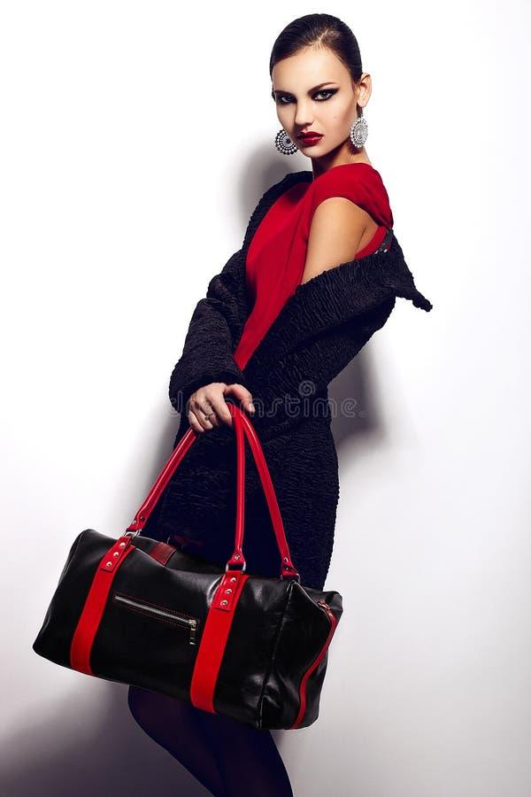 Retrato del primer del encanto del modelo caucásico moreno elegante atractivo hermoso de la mujer joven en vestido rojo con b negr imagen de archivo libre de regalías