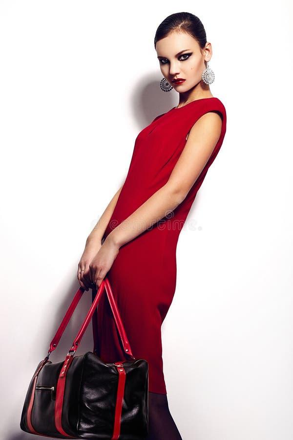 Retrato del primer del encanto del modelo caucásico moreno elegante atractivo hermoso de la mujer joven en vestido rojo con b negr imágenes de archivo libres de regalías