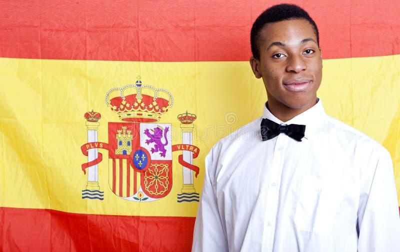 Retrato del primer del hombre joven contra bandera española foto de archivo