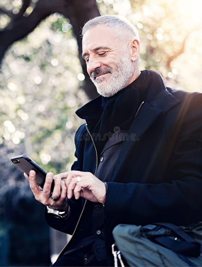 Retrato del primer del mensaje que manda un SMS del hombre de negocios atractivo adulto feliz en smartphone mientras que pasa tie foto de archivo libre de regalías