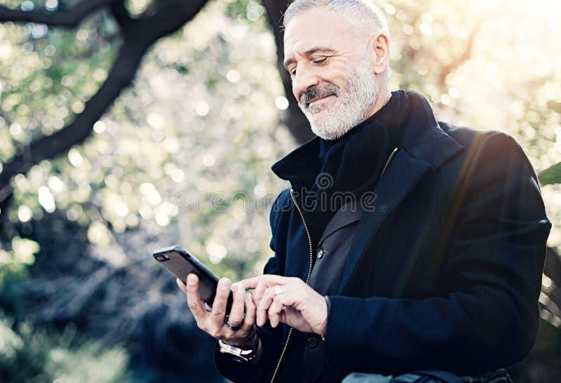 Retrato del primer del mensaje que manda un SMS del hombre de negocios atractivo adulto feliz en smartphone mientras que pasa tie imagen de archivo