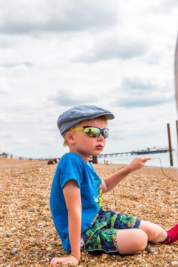 Retrato del primer del muchacho que se sienta en la playa de piedra con las gafas de sol fotos de archivo libres de regalías