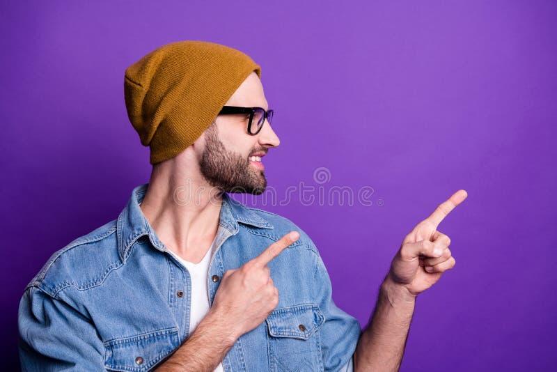 Retrato del primer el suyo él individuo barbudo alegre alegre alegre confiado atractivo agradable que señala el anuncio de dos ín imagenes de archivo