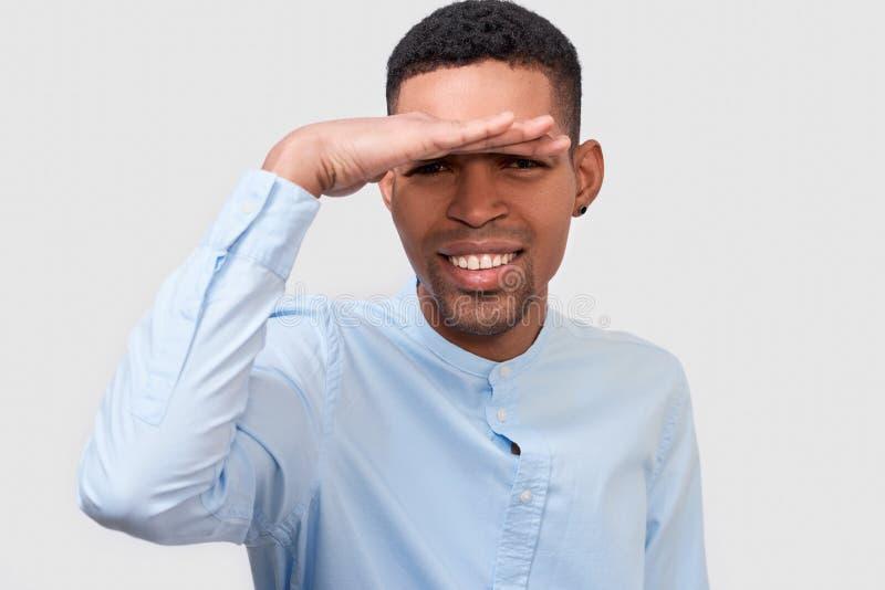 Retrato del primer del hombre afroamericano sonriente que presenta para el anuncio que lleva la camisa azul, mirando lejos con la imagen de archivo
