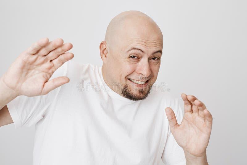 Retrato del primer del hombre barbudo calvo asustado que aumenta las manos a la cubierta algo, bizqueando como si mire luz del so fotografía de archivo