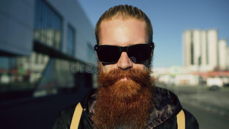 Retrato del primer del hombre barbudo joven del inconformista en gafas de sol que sonríe y que presenta mientras que calle de la  fotos de archivo